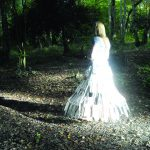 She wander/wonders film directed by Davina Kirkpatrick, music by Sam Hardaker, cameras Ryan Sharp, Mark Guthrie, . A woman in a glass dress walks the paths of the glory wood Dorking and Prussia Cove Cornwall. An embodiment of grief and loss